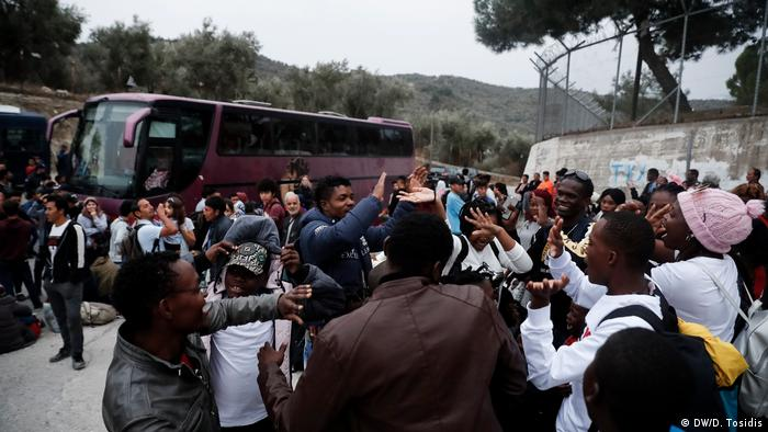 Migrants celebrating their transfer out of the camp