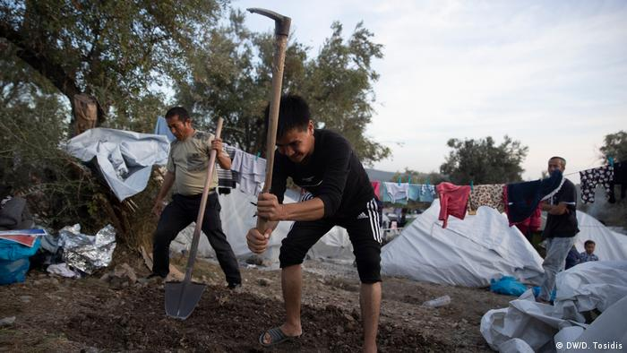 Two men with hoe and spade, digging, against background of tents (DW/D. Tosidis)