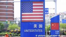 Un cartel con las banderas de China y de EEUU en un centro comercial en Qingdao en la provincia de Shandong en China. Foto tomada el 8 de mayo del 2019. (Chinatopix via AP)  
