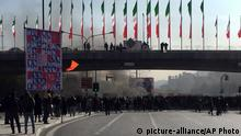 Smoke rises during a protest against raised gasoline prices in Isfahan, Iran