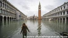 A woman wades through flood water in Venice