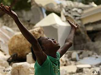 A young girl throws up her arms in despair in front of a devastated building in Port-au-Prince