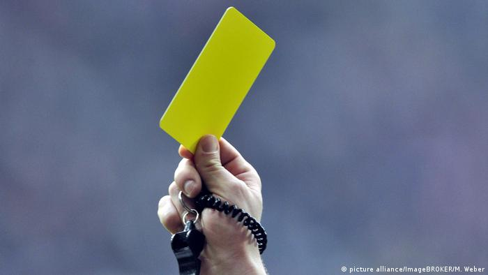 A referee holds up a yellow card