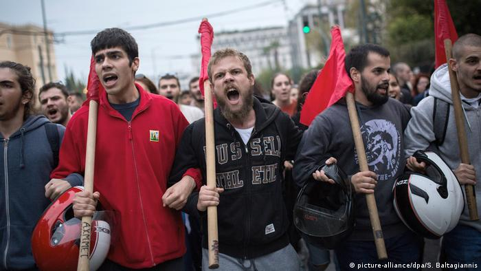 Protesters holding red flags march in Athens