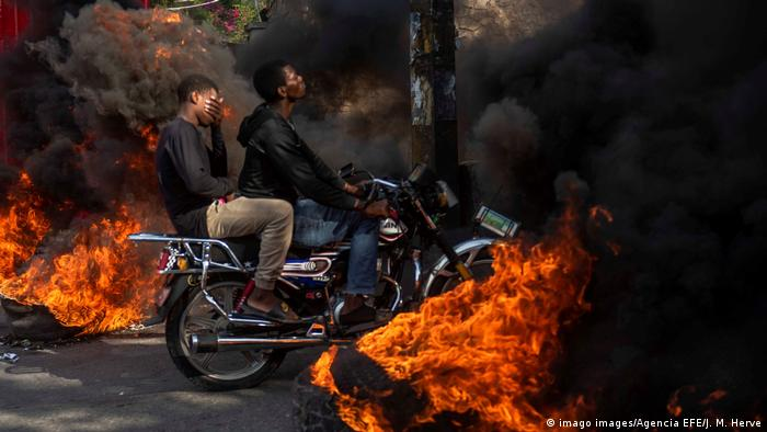 A motorcycle rides through black smoke from burning tires during a protest in Port-au-Prince in November 2019 (imago images/Agencia EFE/J. M. Herve)