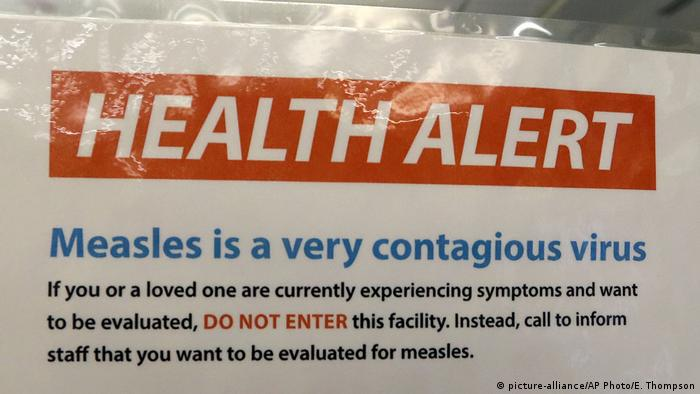 Sign that reads: Health Alert, measles is a very contagious virus (February 13, 2019, AP)