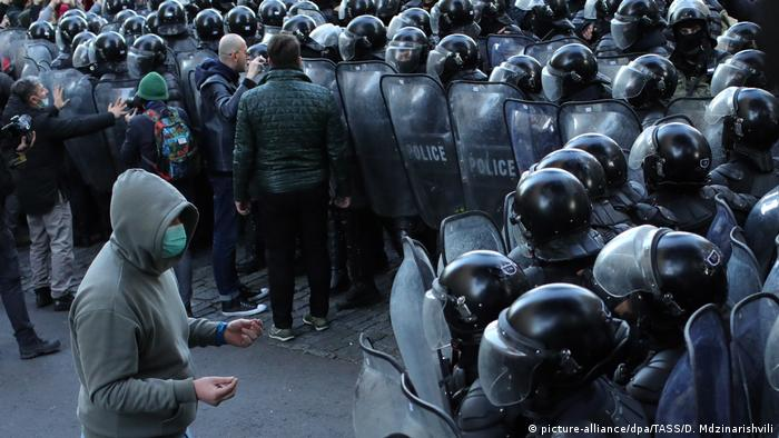 A handful of protesters surrounded by riot police in Tbilisi