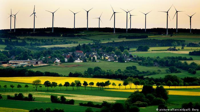 Hinter gelben Feldern und grünen Wiesen stehen auf einer Anhöhe zahlreiche Windräder, auf halber Höhe sind einige Häuser zu erkennen