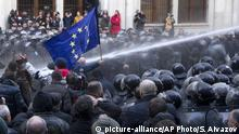 Protester with EU flag hit by water cannon (picture-alliance/AP Photo/S. Aivazov)