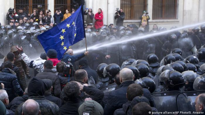 A water cannon shooting at protesters, one of whom is holding an EU flag