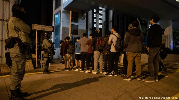 Young people exit through a security control point set up at Hong Kong Polytechnic University