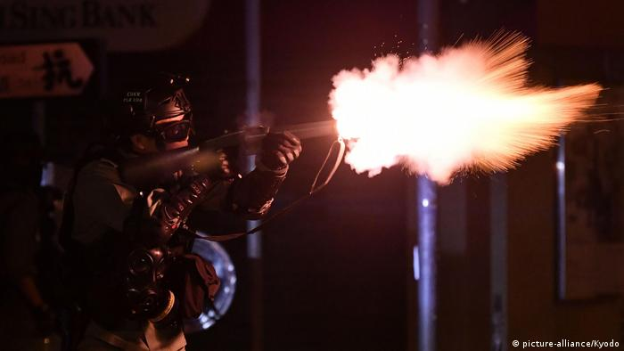 A riot police office fires tear gas at anti-government protesters at Hong Kong Polytechnic University