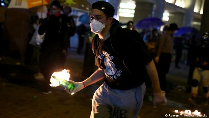 Hong Kong anti-government protester carries a flaming molotov cocktail during protests.