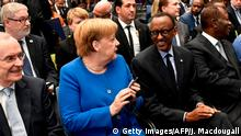 19.11.2019 German Chancellor Angela Merkel (2ndL) talks with Rwanda's President Paul Kagame (3rdL) next to Chairman of the Sub-Saharan Africa Initiative of German Business (SAFRI), Heinz-Walter Grosse (L) before the start of the G20 Investment Summit - German Business and the CwA Countries 2019 on the sidelines of a Compact with Africa (CwA) conference in Berlin on November 19, 2019. (Photo by John MACDOUGALL / POOL / AFP) (Photo by JOHN MACDOUGALL/POOL/AFP via Getty Images)