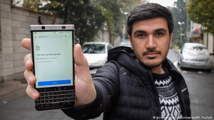 A man shows his phone displaying a message that it is unable to load a website