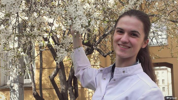 Yelena Tumasov stands next to a tree with blossoms