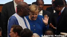 German Chancellor Angela Merkel talks with Burkina Faso's President Roch Marc Christian Kabore as they arrive for a family photo with participants of the G20 Investment Summit - German Business and the CwA Countries 2019 on the sidelines of a Compact with Africa (CwA) in Berlin, Germany November 19, 2019. John MacDougall/Pool via REUTERS