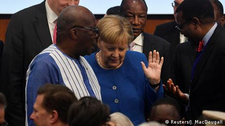 Angela Merkel with the leader of Burkina Faso, Roch Marc Christian Kabore, in a crowd of people