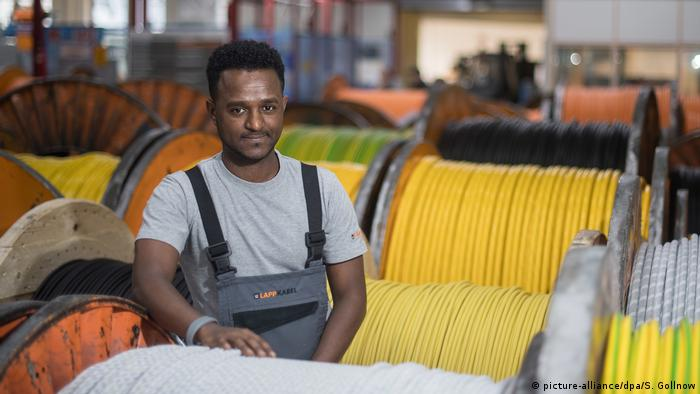 An Eritrean refugee stands between cable reels at the cable manufacturer Lapp in Germany