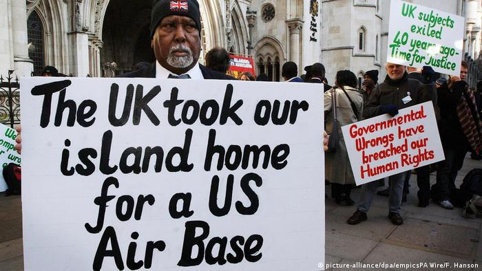 A man holds up a poster reading The UK took our island home for a US airbas