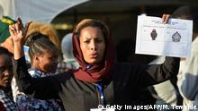 A poll official gives orientation on the ballot paper during the Sidama referendum in Hawassa, Ethiopia, on November 20, 2019. - Polls opened on November 20, 2019, in Ethiopia's ethnic Sidama region in a referendum for a new federal state, a critical vote in a tense region that could embolden others to follow. (Photo by MICHAEL TEWELDE / AFP) (Photo by MICHAEL TEWELDE/AFP via Getty Images)