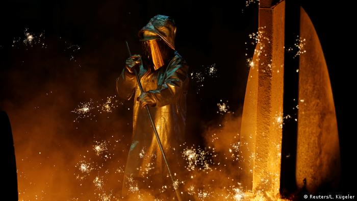 A steel worker stands amid sparks of raw iron coming from a blast furnace at a ThyssenKrupp steel factory in Duisburg, Germany