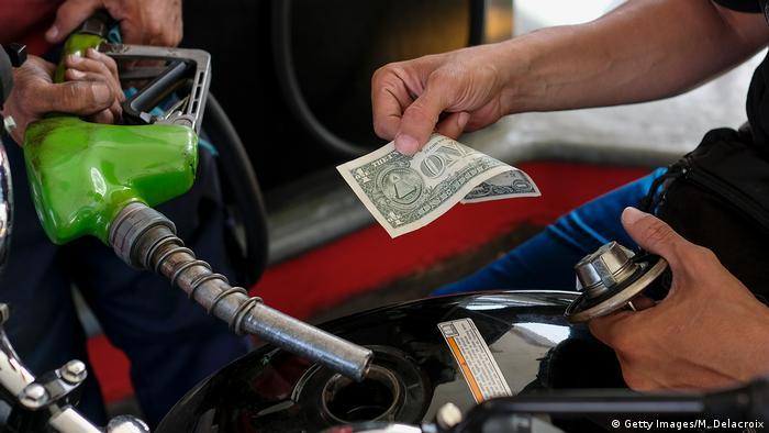 Владелец мотоцикла расплачивается на заправке в Каракасе долларами США