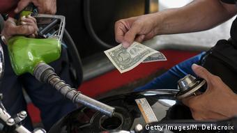 Un hombre compra gasolina con dólares en Venezuela.