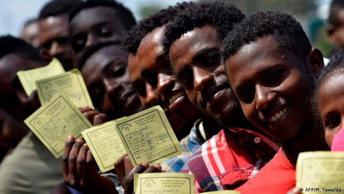 Young Ethiopian voters display voters cards