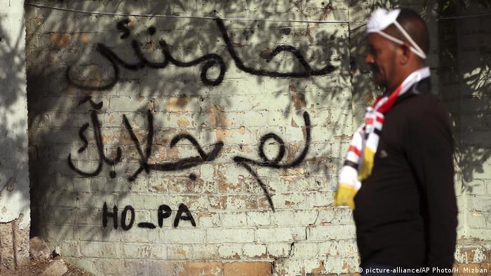 Irak Bagdad Protestierender vor Schriftzug (picture-alliance/AP Photo/H. Mizban)