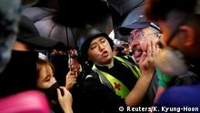 Pastor Alan Keung pacifies a man arguing with protesters who blocked the road during an anti-government protest in Hong Kong, China October 31, 2019. REUTERS/Kim Kyung-Hoon SEARCH HONG KONG PASTOR FOR THIS STORY. SEARCH WIDER IMAGE FOR ALL STORIES