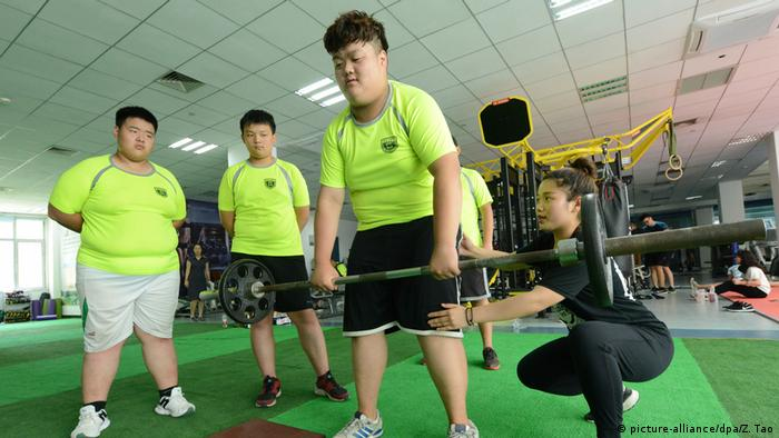 Übergewichtige Jungs versuchen in Zhengzhou ein Gewicht zu heben (picture-alliance/dpa/Z. Tao)