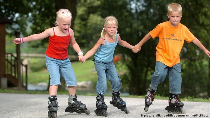 Zwei Mädchen und ein Junge laufen mit Rollerblades (picture-alliance/Bildagentur-online/McPhoto)