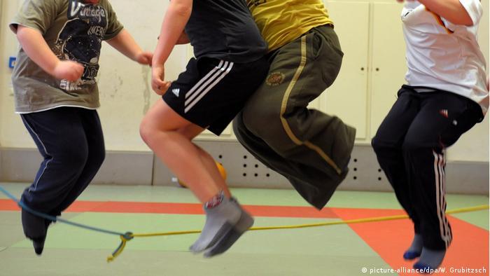 Übergewichtige Kinder hüpfen in einer Sporthalle (picture-alliance/dpa/W. Grubitzsch)