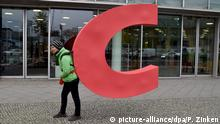 A Greenpeace activists carries the C from the CDU headquarters in Berlin, Germany (picture-alliance/dpa/P. Zinken)