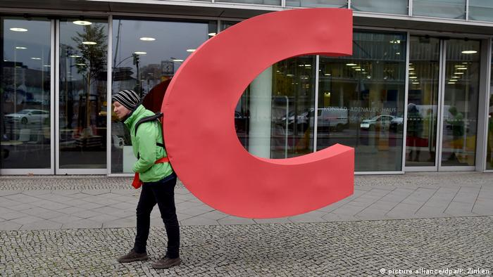 A Greenpeace activists carries the C from the CDU headquarters in Berlin, Germany