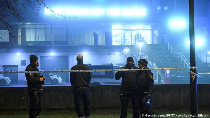 Swedish police officers stand guard outside an office building after an explosion in the Rosengard district of Malmo
