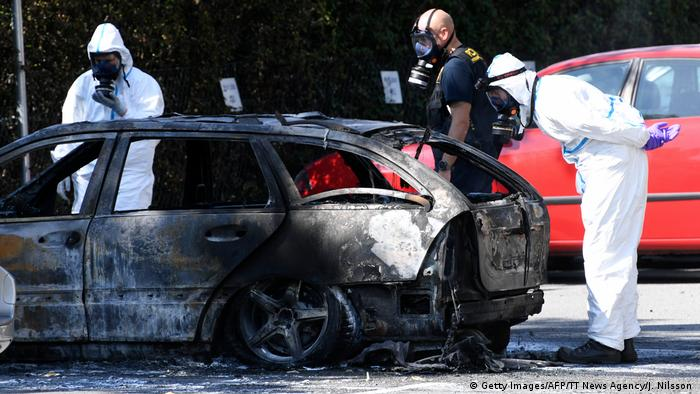 Police inspect a burned out car near the scene where Karolin Hakim was killed in Malmo