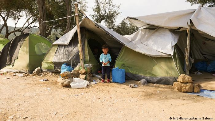 A child stands outside a tent on Lesbos