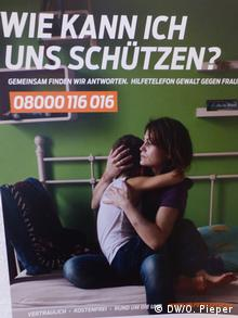 Poster showing woman and child on a bed, with a phone number (DW/O. Pieper)