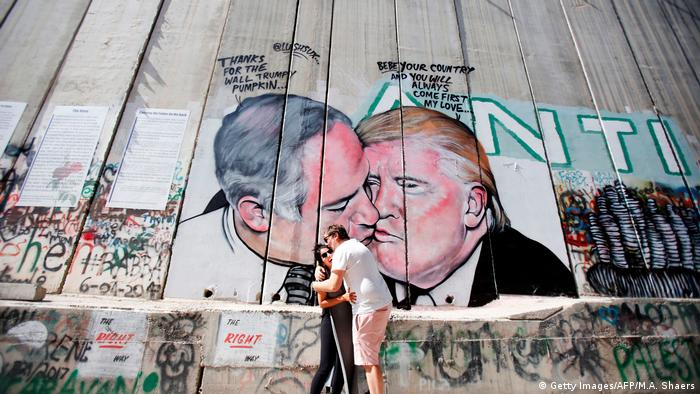 A couple hugs in front of a wall in Bethlem that depicts Donald Trump and Benjamin Netanyahu kissing one another