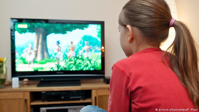 Young girl watching cartoon on TV