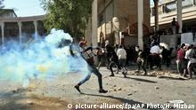 An anti-government protester throws throw back a tear gas canister fired by police during clashes in Baghdad, Iraq, Friday, Nov. 22, 2019. Iraq's massive anti-government protest movement erupted Oct. 1 and quickly escalated into calls to sweep aside Iraq's sectarian system. Protesters occupy several Baghdad squares and parts of three bridges in a standoff with security forces. (AP Photo/Hadi Mizban) |