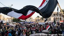 BAGHDAD, IRAQ - NOVEMBER 21: A flag waves over Tahrir Square on November 21, 2019 in Baghdad, Iraq. Thousands of demonstrators have occupied Baghdad's center Tahrir Square since October 1, calling for government and policy reform. For many, Tahrir Square, which protesters are calling a free state with a failed state, has become a symbol of potential change as it offers free medicine, food, electricity and even hot showers, all provided and supported by the protesters. Ali says she and her family will chop onions sometimes for up to 12 hours a day to support the protesters. (Photo by Erin Trieb/Getty Images)