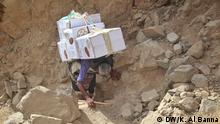 Main title: Work of the elderly in Yemen Photo's title : An elderly Yemeni on his back is a load in Taiz countryside Place & Date: November 2019, Sana'a Copyright / Photographer: Khaled Al Banna, exclusive for DW