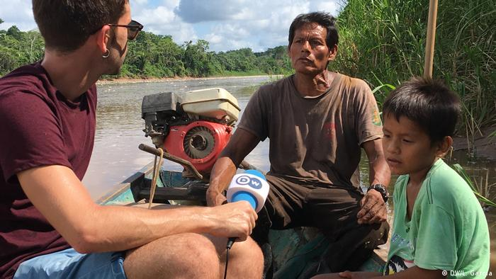 Enrique Anarte, de DW, junto a Rodrigo 'comunero Walter' y su hijo en el bote con el que pesca cada mañana en el río Aguaytía.