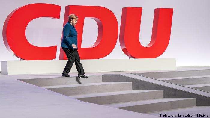 Angela Merkel walking down steps in front of a huge CDU logo (picture-alliance/dpa/K. Nietfeld)