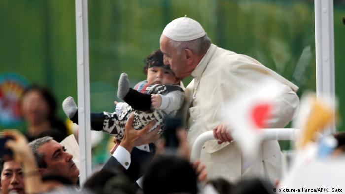 Pope Francis kisses a child