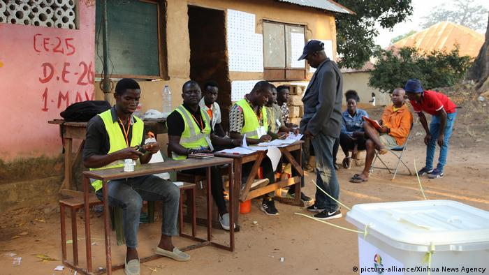 Electoral workers verify a voter's identity at an outdoor polling station in Bissau