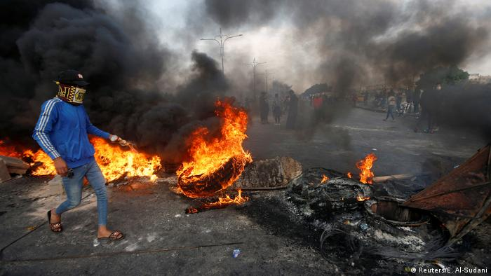A protester is seen near a burning tire during ongoing anti-government protests in Basra